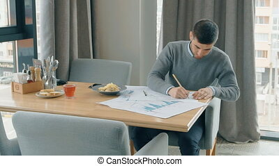 Young man is working on blueprint, sitting at table in cafe interior.