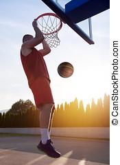 Young man jumping and making a fantastic slam dunk playing stree