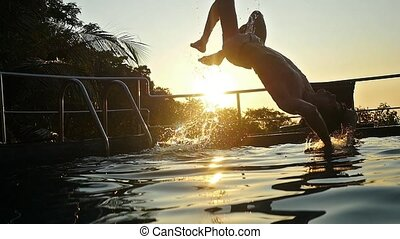 Young man jumping back flip in swimming pool water at Sunset through the sun and water splashing with beautiful bokeh. slow motion. 1920x1080
