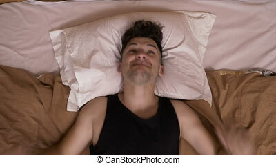 Young man jumping in bed feeling very furious and desperate...