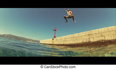 Young man jumping in the sea from a dock