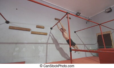 Young man jumping on a metal structure during training in gym. Caucasian guy showing acrobatic tricks indoor. Concept of sportive lifestyle. Side view Close up Slow motion