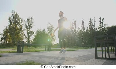 Young man jumping rope outdoors.