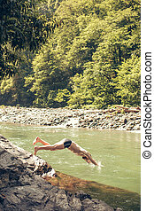 Young man jumping to the water of lake shore. Tourist Relax concept.