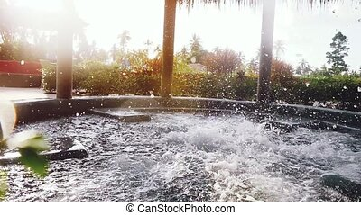 Young man jumps in to the jacuzzi during sunset an outdoor...