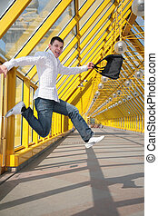 young man jumps with bag on footbridge
