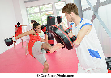 young man kicking a padding