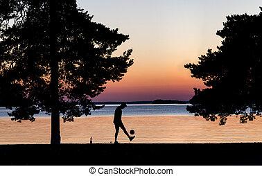 Young man kicking ball