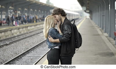 Young man kissing and saying and waving goodbye to his girlfriend in train station before leaving