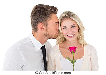 Young man kissing happy woman