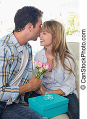 Young man kissing woman with flowers and gift box