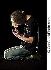 A young man kneels and prays in the dark