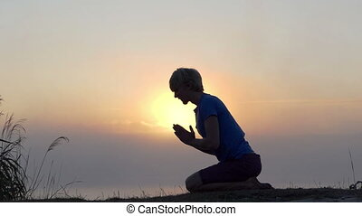Young man kneels and prays on a lake bank at sunset in slo-mo
