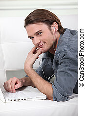 Young  man laid in front of computer with earphones