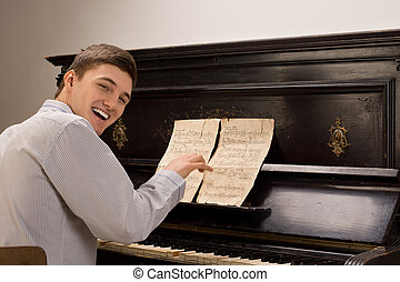 Young man laughing as he sits playing the piano