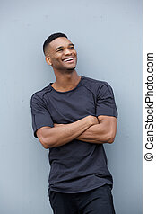 Young man laughing with arms crossed
