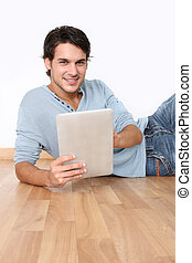 Young man laying on the floor with digital tablet