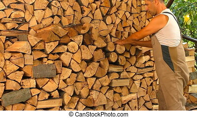 Young man lays on chopped wood in the woodpile - Young man...