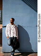 Young man leaning against a city wall