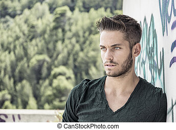 Young man leaning against colorful wall
