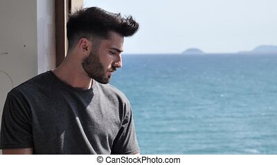 Young man leaning against window with sea behind