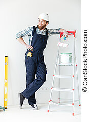 Young man leaning on ladder looking away while making repair