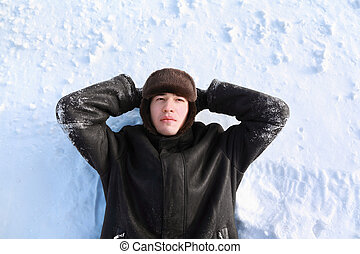 Young man lies on back on snow locate hands for head and looks dreamily