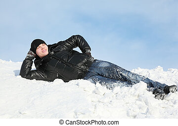 Young man lies on snow support  palm and looks far in sky