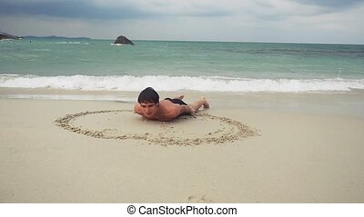 Young man lies on the sand draws a heart symbol on the wet sand on the seashore. slow motion.