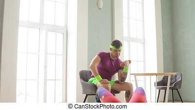 Young man lifting dumbbell and looking on his wife doing glute bridge exercise.