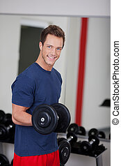 Young Man Lifting Dumbbell In Gym