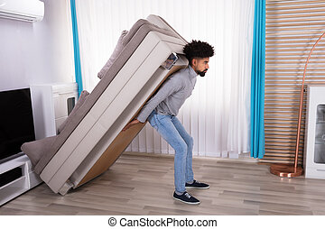 Young Man Lifting Sofa