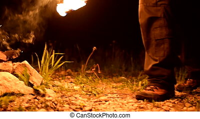Young man lights two fire torches. Low key. Vertical pan. ...