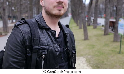 Young man listen to music on smartphone in city park