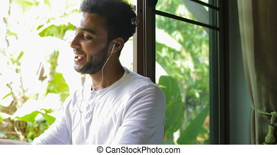 Young Man Listen To Music On Tablet Computer With Earphones...