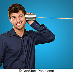 Young Man Listening From Tin Can Telephone