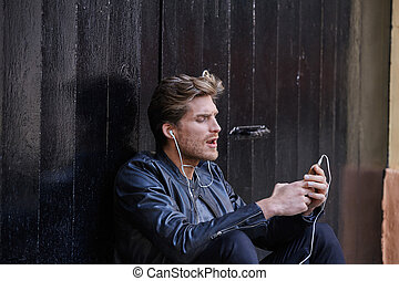 Young man listening music smartphone earphones