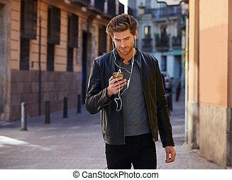 Young man listening music smartphone earphones