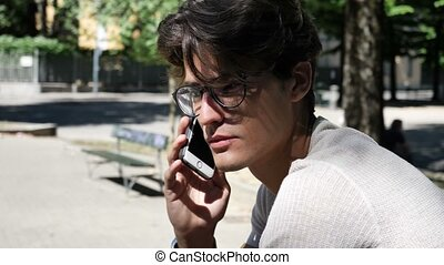 Young man listening then sending voice recording on cell phone