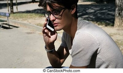 Young man listening then sending voice message with cell phone