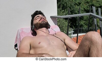 Young Man Listening to Music on Lounge Chair - Shirtless Fit...