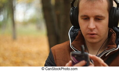 Young man listening to music on smartphone on the nature