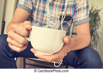young man listening to music while having a coffee or tea