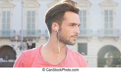 Young Man Listening to Music with Earphones - Close up of...