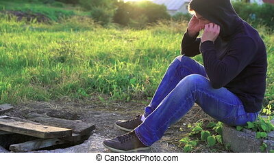 Young man listening to the music in earphones on the nature