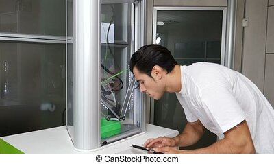 Young man looking at 3d printer machine - Brunet adult man...
