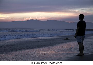 Young Man Looking at Beach Sunset