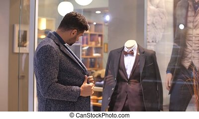 Young man looking at suit in a shop window