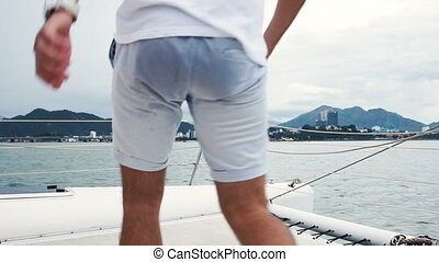 Young man looking at the ocean and rise hands while enjoying a cruise on yacht