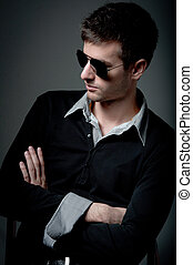 Young man looking in the opposite side wearing sunglasses